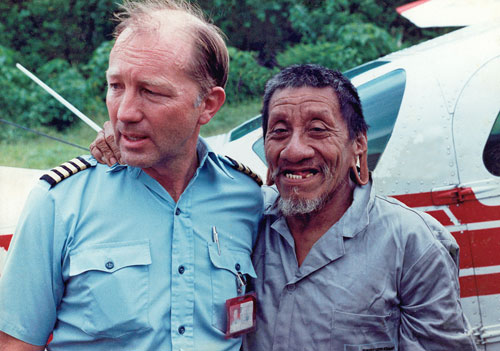 Aviation & Space Writer, James Rush Manley, stands with a Huaorani man in front of airplane
