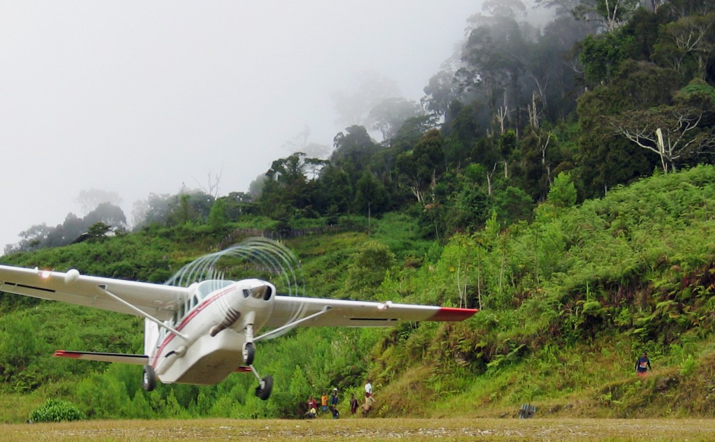 Propeller of plane taking off from jungle airstrip leaves spiraling condensation trail