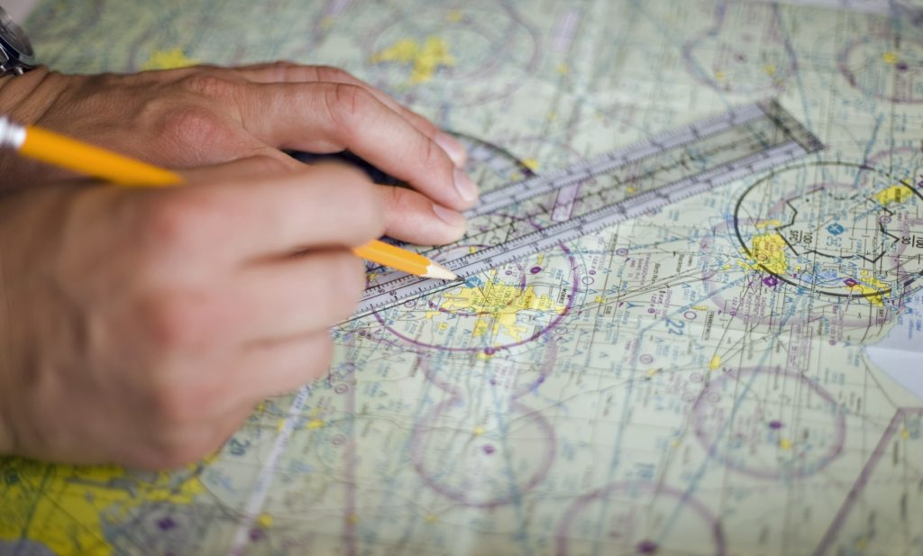 Aviation & Space Writer, James Rush Manley plots a straight line on an aviation map