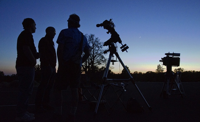Amateur astronomers standby telescopes waiting for dark