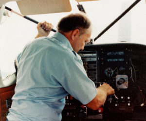 Avionics tech installing radios in a C-206 panel