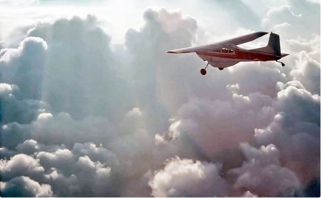 Finding new focus is like this Cessna C-185 flying over gray clouds into the sunlight
