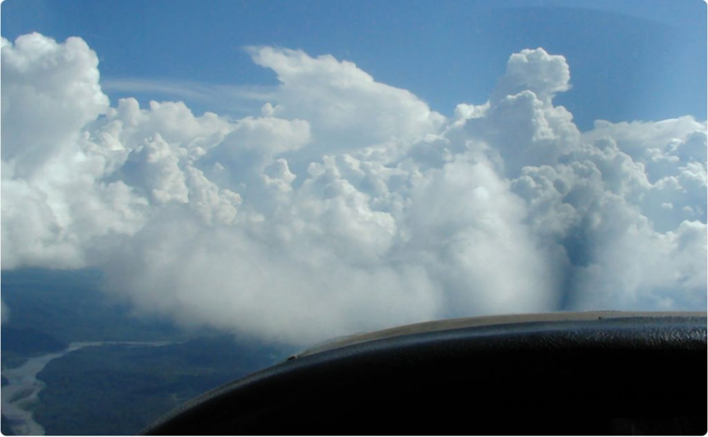 View from pilot's seat of small aircraft flying above clouds
