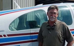 bearded man stands next to a Beechcraft Bonanza