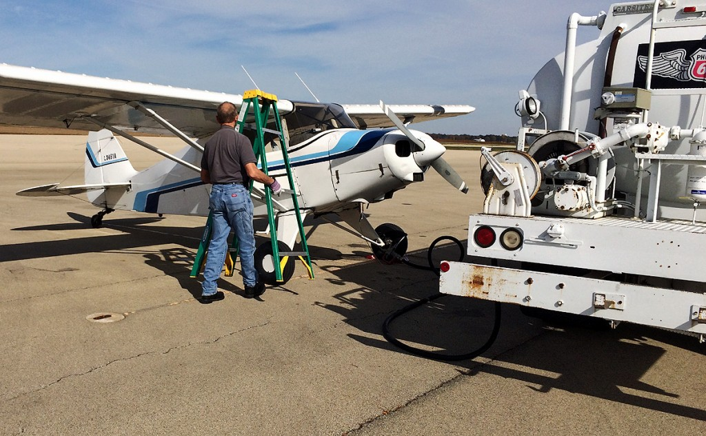 man places refueling ladder in front of aircraft wing