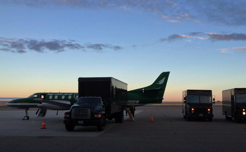 Unloading 3 trucks into twin engine airplane