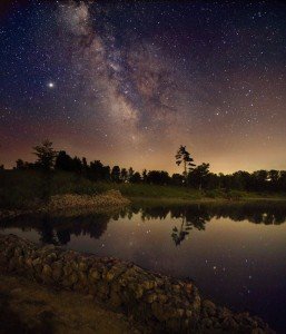 Milky Way in night sky above a lake shore