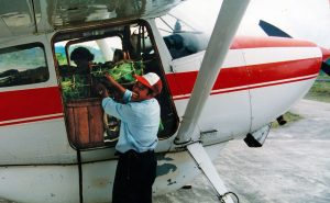Smiling man loading cargo into a single engine airplane