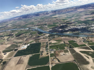 Focusing on an aerial view of farm land from banked airplane