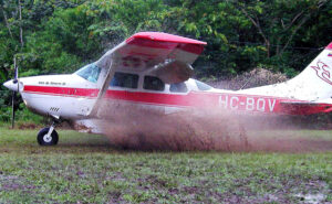 a cool single engine, high wing airplane landing on wet jungle airstrip